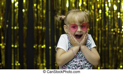 Child dancing, show amazement, fooling around, smiling, looking surprised shocked. Little fun blonde kid teen teenager girl 4-5 years old in sunglasses posing isolated on background with foil curtain