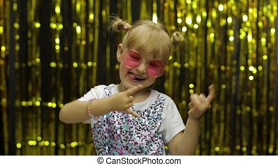 Child dancing waving hands fooling around. Girl 4-5 years old posing on background with foil curtain