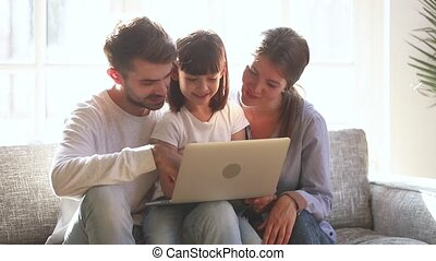 Child daughter laughing looking at laptop watching cartoons with parents