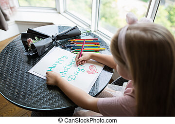 Child daughter painting postcard for mom. Girl sitting at home on table, next lying pink flower for mother. Mother day concept
