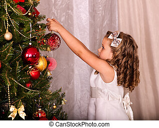 Child decorate on Christmas tree.