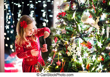 Child decorating Christmas tree - Little girl in red knitted...