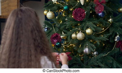 Child decorating Christmas tree with toys - Rear view of...