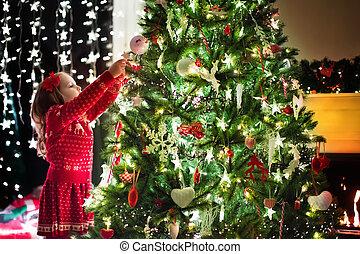 Child decorating Christmas tree. Xmas for kids - Little girl...
