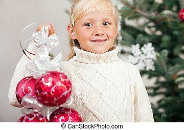 Child decorating the Christmas tree