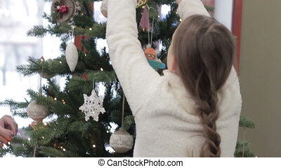 Child decorating the Christmas tree. Waiting for the New...