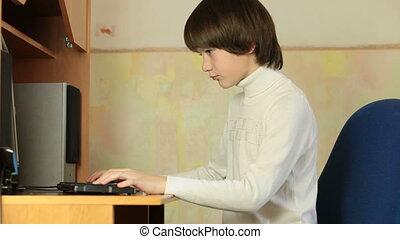 Child Deep in Desktop Computer Game - Teen Boy Playing...