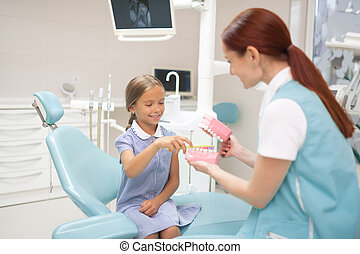 Child dentist giving girl a lesson of teeth brushing