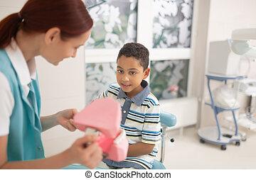 Child dentist showing teeth model to cute dark-skinned boy