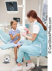 Child dentist wearing uniform teaching girl to brush teeth