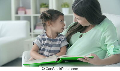 Child Development - Close up of mother reading to her little...