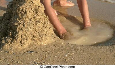 Child digging pit, beach. Sand and water.