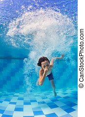 Child diving underwater in swimming pool