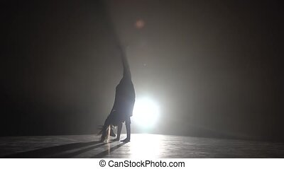 Child does a handstand in the studio. Black smoke background. Silhouette. Light from behind. Slow motion