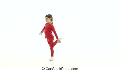 Child does acrobatic movements. White background. Slow...