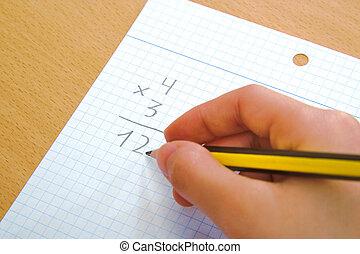 Child doing a math multiplication as homework. - Child doing...