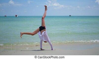 child doing gymnastics on the beach on a Sunny day