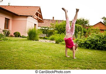 Child doing handstand in backyard