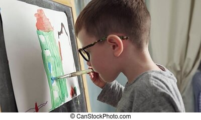 Child drawing house - Cute little boy paints house with...