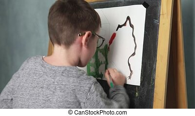 Child drawing house - Little boy paints watercolors