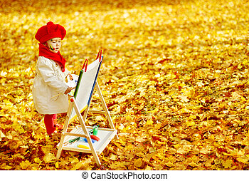 Child drawing on easel in Autumn Park. Creative kids ...