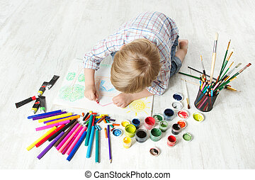 Child drawing picture with crayon  in album using a lot of painting tools. Top view. Creativity concept.