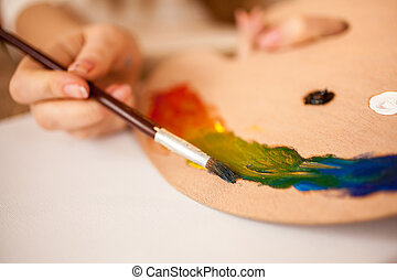 child drawing rainbow by oil paint on wooden pallet
