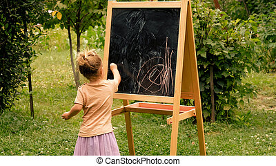 Child drawing with chalk at the blackboard