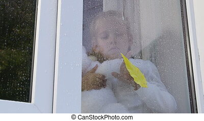 Child draws on the window pane in raindrops with yellow leaf in autumn
