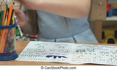 Child draws the pictures in the copybook indoors