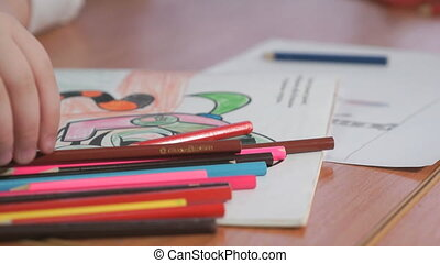 Child draws the pictures using color pencils - Close-up of ...