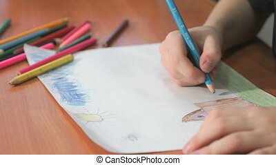 Child draws the pictures using color pencils - Close-up of...