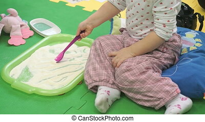 Child draws the spoon on the sand in the tray - Child sits...