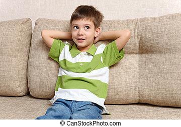 Child dreams sitting on sofa