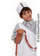 Child dressed as a butcher with a link of sausages