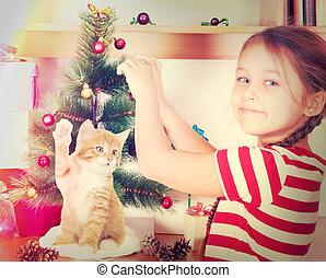 child dresses up Christmas tree