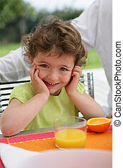 Child drinking a class of freshly squeezed orange juice