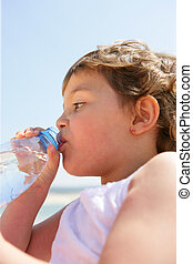 Child drinking from a bottle of water