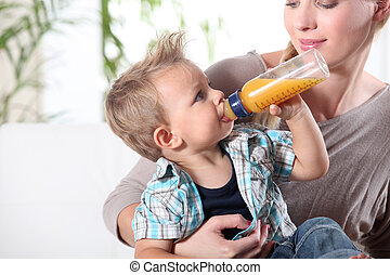 Child drinking juice in his mother's lap