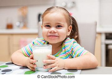 Child drinking milk in the kitchen at home