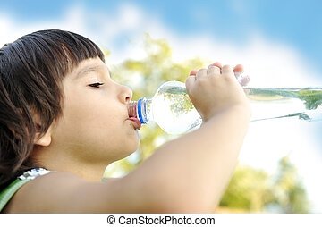 Child drinking pure water in nature