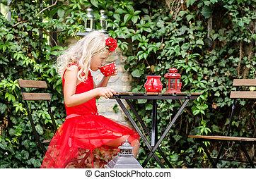 child drinking tea in the garden