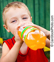 Child drinking unhealthy bottled soda - Thirsty child...