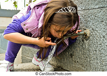 Child drinking water from a fountain