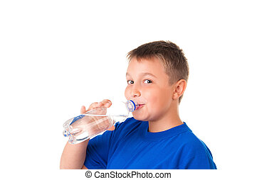 Child drinks clean water from bottle isolated on white background. The boy is wearing a blue T-shirt