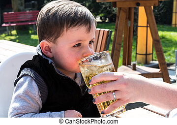 Child drinks juice from a glass