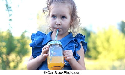 Child drinks orange fresh in the summer. Portrait of a little girl who enjoys smoothies through a tube