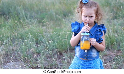 Child drinks orange fresh in the summer.