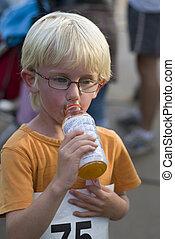 child drinks sportsdrink after the childrunning