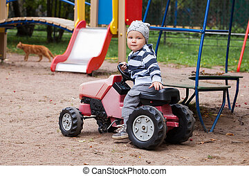 Child driving a car toy on playground